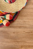 Mexican background sombrero wood copy space vertical. Mexican background with sombrero straw hat, maracas and traditional serape blanket or rug on a wood floor Stock Images