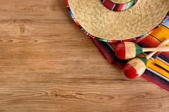 Mexico, Mexican sombrero wood background, copy space. Mexican background with sombrero straw hat, maracas and traditional serape blanket or rug on a wood floor Royalty Free Stock Photo