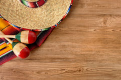 Mexico, Mexican sombrero wood background, copy space. Mexican background with sombrero straw hat, maracas and traditional serape blanket or rug on a wood floor Stock Photography