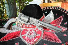 Cinco de mayo Mexican sombrero fiesta. Sequin and decorative ornate mexican hat ready for a fiesta with a gun and cactus in background royalty free stock images