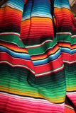 Poncho Mexican serape background woven rug fiesta style. Poncho Mexican serape background Woven traditional bright ornate rug ready to wear for a fiesta royalty free stock images
