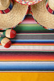 Mexican background vertical copy space sombreros maracas. Mexican background with sombrero straw hat, maracas and traditional serape blanket or rug.  Space for Royalty Free Stock Photo
