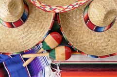 Mexican sombrero and maracas. Mexican scene with sombrero straw hat, maracas and traditional serape blanket or rug Stock Photos