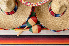 Mexican sombreros and maracas. Mexican scene with sombrero straw hat, maracas and traditional serape blanket or rug.  Space for copy Royalty Free Stock Photo