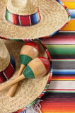 Mexican sombreros with maracas and traditional serape blankets. Mexican scene with sombrero straw hat, maracas and traditional serape blanket or rug Royalty Free Stock Image