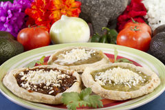 Mexican Sopes Dish. Sopes which is a thick tortilla with red or green salsa and topped with crumbled cheese Stock Photos