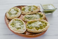 Mexican sopes with grated cheese and green salsa, mexican food spicy in mexico. Memelas royalty free stock images