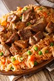 Mexican spicy rice with fried pork close-up. vertical stock photo