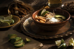 Mexican spicy soup with lime, tortilla, avocado and cream Royalty Free Stock Images