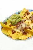 Mexican starter. Nachos with avocado dip, cheese and bacon royalty free stock photos