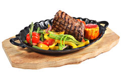 Mexican steak with vegetables in cast iron oval serving platter. Mexican steak in cast-iron oval serving dish with handles on a wooden plate, isolated on white Royalty Free Stock Image