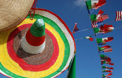 Mexican strawhat with many flags on blue sky Royalty Free Stock Photo