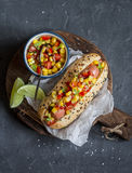 Mexican street style hot dog with corn salsa on a wooden cutting board on dark background. Top view royalty free stock photo