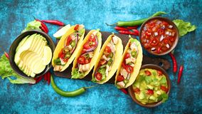 Mexican taco with chicken meat, jalapeno, fresh vegetables served with guacamole. And tomato salsa. Latin american food. Placed on blue table stock footage