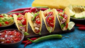 Mexican taco with chicken meat, jalapeno, fresh vegetables served with guacamole. And tomato salsa. Latin american food. Placed on blue table stock video footage