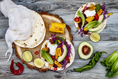 Mexican tacos with avocado, slow cooked meat, grilled corn, red cabbage slaw and chili salsa on rustic stone table. stock images