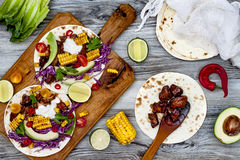 Mexican tacos with avocado, slow cooked meat, grilled corn, red cabbage slaw and chili salsa on rustic stone table. Stock Photo