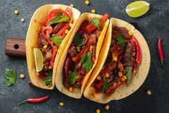 Mexican tacos with beef, vegetables and salsa. Tacos al pastor on wooden board on black background. Top view stock photography