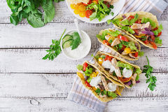 Mexican tacos with chicken, black beans and fresh vegetables and tartar sauce
