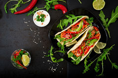 Mexican tacos with chicken fillet in tomato sauce and salsa Stock Photo