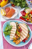 Mexican tacos with grilled vegetables and salmon. Healthy food for lunch. Fast food. Copy space.  Royalty Free Stock Image