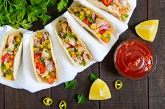 Mexican tacos with meat, corn, tomatoes, sweet pepper, red onions in a wheat tortilla Royalty Free Stock Photo