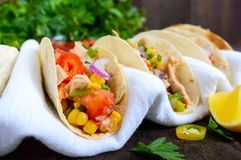Mexican tacos with meat, corn, tomatoes, sweet pepper, red onions in a wheat tortilla Royalty Free Stock Photos
