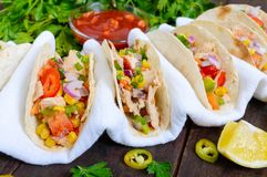 Mexican tacos with meat, corn, tomatoes, sweet pepper, red onions in a wheat tortilla stock photo