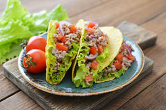 Mexican tacos. With meat, onion and tomato on plate on wooden background Royalty Free Stock Images