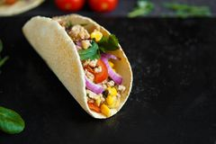 Mexican tacos with pork, vegetables and spices on a black stone plate on a dark background with ingredients for tacos stock image