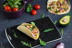 Mexican tacos with pork, vegetables, tomatoes, avocado and spices on a black stone plate on a dark background with ingredients for stock photo