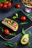 Mexican tacos with pork, vegetables, tomatoes, avocado and spices on a black stone plate on a dark background with ingredients for royalty free stock photo