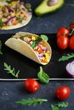 Mexican tacos with pork, vegetables, tomatoes, avocado and spices on a black stone plate on a dark background with ingredients for stock photos