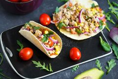 Mexican tacos with pork, vegetables and spices on a black stone plate on a dark background with ingredients for tacos stock photography