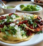 Mexican pork tacos. Traditional mexican tacos al pastor, pork meat, with fresh cilantro, onions and pineapple Stock Photo