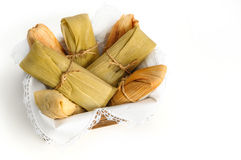 Mexican tamales made of corn and chicken isolated on white. Tamales, Mexican dish made with corn dough, chicken and chili, wrapped with a corn leaf Royalty Free Stock Photos
