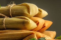 Mexican tamales made of corn and chicken isolated on white. Tamales, Mexican dish made with corn dough, chicken and chili, wrapped with a corn leaf Stock Photos