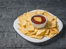 Mexican tortilla chips in a bowl with sauce and mustard on the table on a white plate with sauce in the center. stock photos