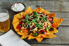 Mexican tortilla chips with  cheese  tomato black olives pepper sauce Royalty Free Stock Photo