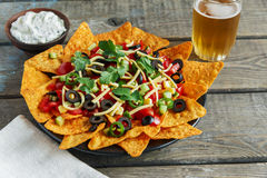 Mexican tortilla chips with cheese tomato black olives pepper sauce Stock Photo