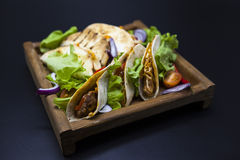Mexican Tortilla with meat, beef and stewed vegetables and spicy sauce on a wooden tray. Stock Photo