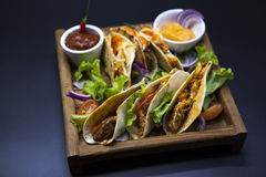 Mexican Tortilla with meat, beef and stewed vegetables and spicy sauce on a wooden tray. Stock Photos