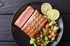 Mexican tuna steak with avocado cucumber salsa closeup. horizontal view from above. Mexican tuna steak with avocado cucumber salsa closeup on a plate. Top view stock image
