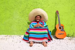 Mexican typical lazy topic man guitar poncho sit. In green wall Stock Image