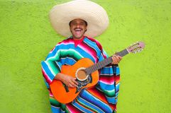 Mexican typical man playing guitar poncho. On green wall Stock Images