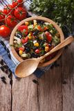 Mexican vegetable salad in a wooden bowl, close-up vertical top Royalty Free Stock Image