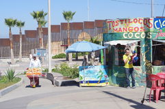 Mexican vendors next to USA-Mexico Wall Stock Image