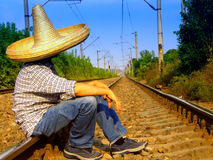 Mexican waiting the train. Mexican man with a sombrero sitting on the train rail Stock Photo