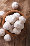 Mexican wedding cookies close up in a wooden bowl. vertical top Royalty Free Stock Photo