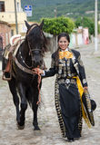 Mexican woman and black horse. Young Mexican woman in traditional outfit walking with black Andalusian horse on cobblestone street in Mexican village royalty free stock photos
